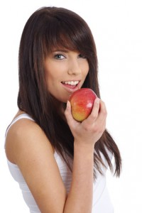 young woman holding  apple. Isolated over white